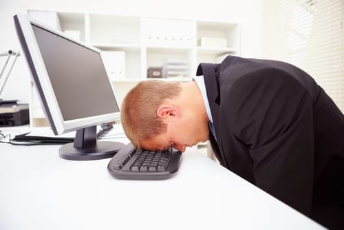 man with head down on computer keyboard