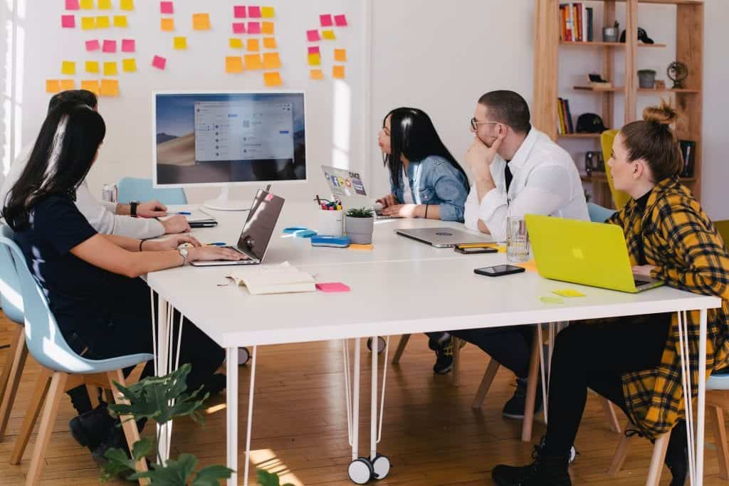 5 UX designers gathered around a table looking at a large computer screen in front of a wall full of colorful sticky notes