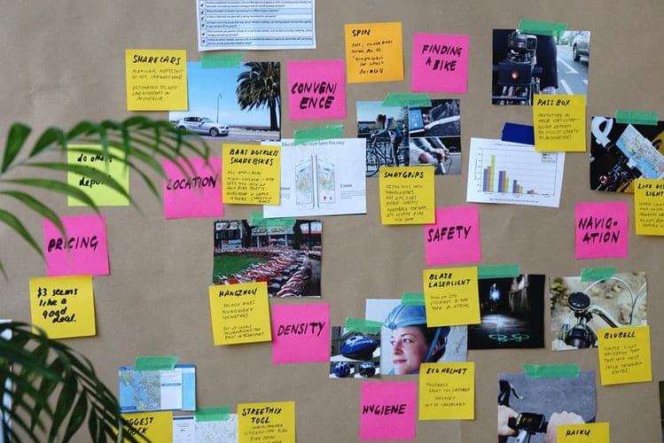 colorful sticky notes and photos from on brainstorming wall