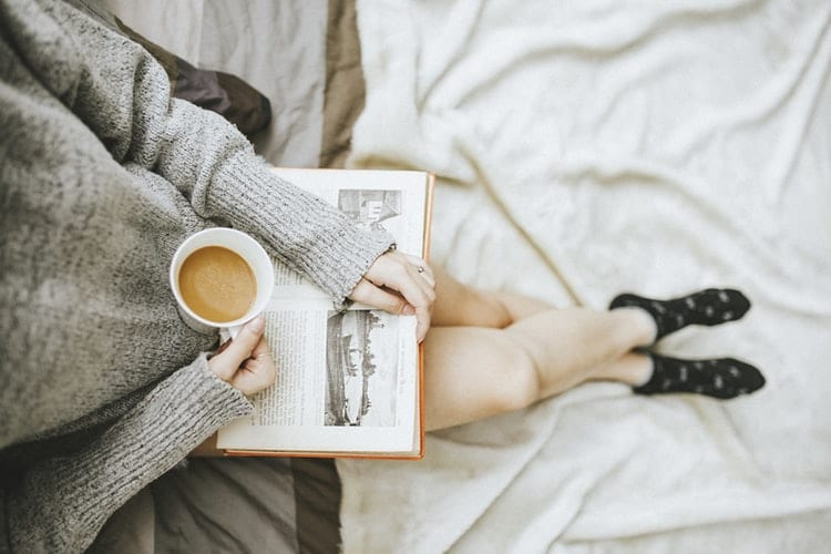 woman reading and relaxing in cozy setting