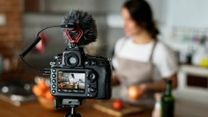 woman filming cooking video in kitchen