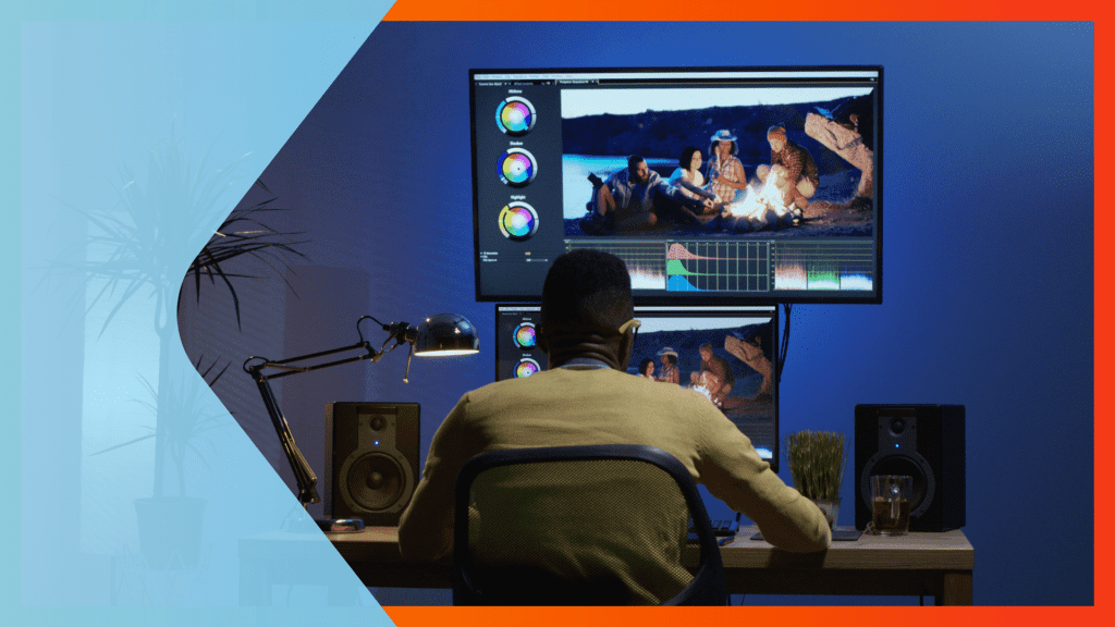 Man sitting at a computer with a large monitor as he's editing a video.
